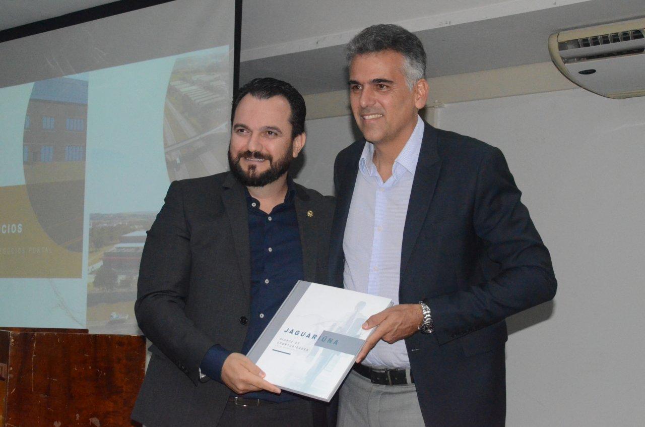 Secretário Valdir entrega um livro para o prefeito Gustavo durante o lançamento